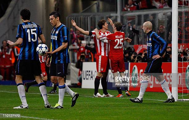 Mario Gomez of Bayern Muenchen celebrates his first goal with teammate Thomas Mueller as Andrea Ranocchia Lucio and Esteban Cambiasso of Inter Milan...