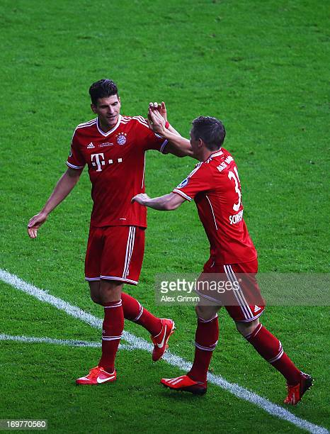 Mario Gomez of Bayern Muenchen celebrates with team mate Philipp Lahm of Bayern Muenchen as he scores their second goal during the DFB Cup Final...