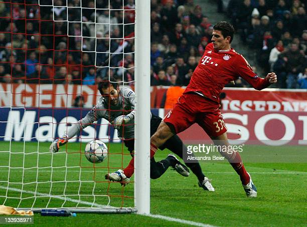 Mario Gomez of Bayern Muenchen scores his first goal against goalkeeper Diego Lopez of Villareal during the UEFA Champions League group A match...