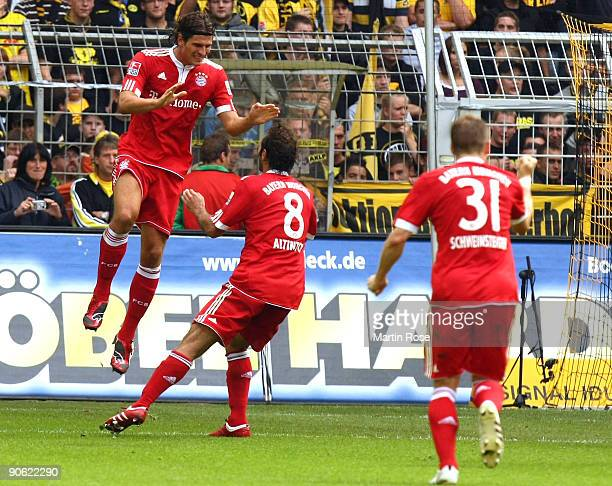 Mario Gomez of Bayern Munich celebrates after scoring his team' first goal with team mates during the Bundesliga match between Borussia Dortmund and...