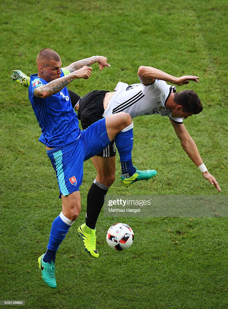 Mario Gomez of Germany and Martin Skrtel of Slovakia compete for the ball during the UEFA EURO 2016 round of 16 match between Germany and Slovakia at Stade Pierre-Mauroy on June 26, 2016 in Lille, France.