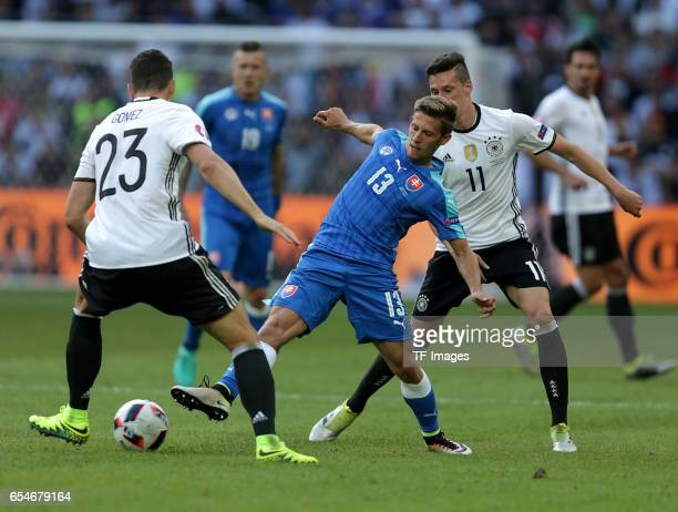 Mario Gomez of Germany and Patrik Hrosovsky of Slovakia and Julian Draxler of Germany battle for the ball during the UEFA EURO 2016 round of 16 match...