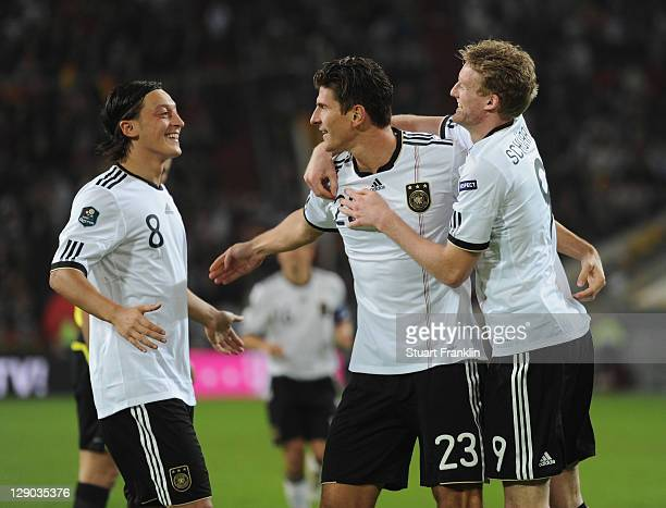 Mario Gomez of Germany celebrates scoring his goal with Mesut Oezil and Andre Schueller during the UEFA EURO 2012 Group A qualifying match between...