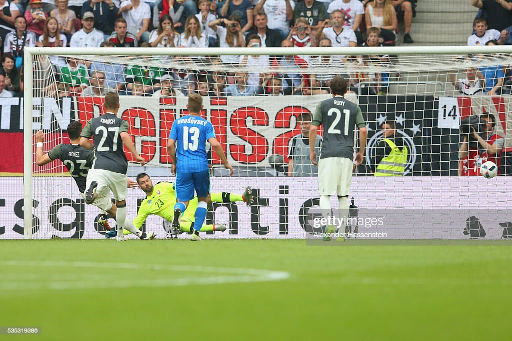 Mario Gomez (L) of Germany scores the opening goal with a penalty past Matus Kozacik, keeper of Slovakia during the international friendly match between Germany and Slovakia at WWK-Arena on May 29, 2016 in Augsburg, Germany.