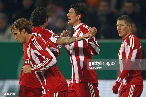 Mario Gomez of Muenchen celebrates his team's first goal with team mates Andreas Ottl Hamit Altintop and Bastian Schweinsteiger during the DFB Cup...