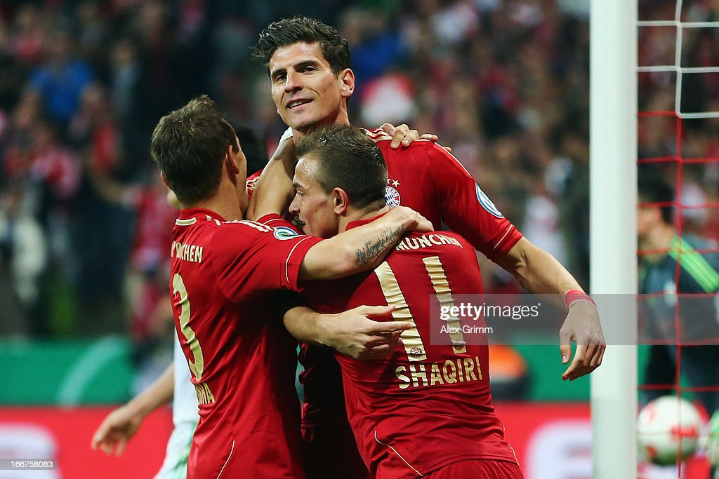 Mario Gomez (back) of Muenchen celebrates his team's fourth goal with team mates Rafinha and Xherdan Shaqiri (R) during the DFB Cup Semi Final match between Bayern Muenchen and VfL Wolfsburg at Allianz Arena on April 16, 2013 in Munich, Germany.