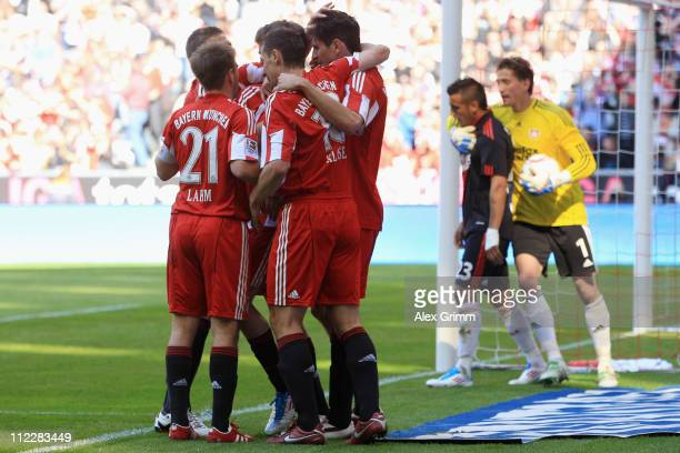 Mario Gomez of Muenchen celebrates his team's second goal with team mates as goalkeeper Rene Adler of Leverkusen comforts his team mate Arturo Vidal...