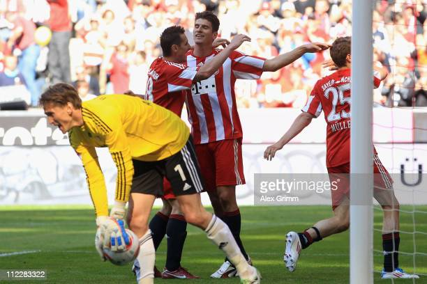 Mario Gomez of Muenchen celebrates his team's third goal with team mates Miroslav Klose and Thomas Mueller as goalkeeper Rene Adler of Leverkusen...