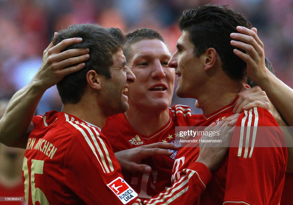 Mario Gomez (R) of Muenchen celebrates scoring the first team goal with his team mates <a gi-track='captionPersonalityLinkClicked' href=/galleries/search?phrase=Thomas+Mueller&family=editorial&specificpeople=5842906 ng-click='$event.stopPropagation()'>Thomas Mueller</a> (L) and <a gi-track='captionPersonalityLinkClicked' href=/galleries/search?phrase=Bastian+Schweinsteiger&family=editorial&specificpeople=203122 ng-click='$event.stopPropagation()'>Bastian Schweinsteiger</a> (C) during the Bundesliga match between FC Bayern Muenchen and Hertha BSC Berlin at Allianz Arena on October 15, 2011 in Munich, Germany.