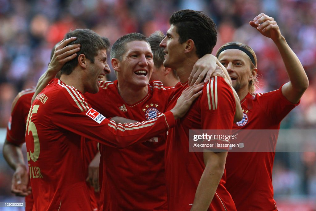 <a gi-track='captionPersonalityLinkClicked' href=/galleries/search?phrase=Mario+Gomez+-+Voetballer&family=editorial&specificpeople=635161 ng-click='$event.stopPropagation()'>Mario Gomez</a> (R) of Muenchen celebrates scoring the first team goal with his team mates <a gi-track='captionPersonalityLinkClicked' href=/galleries/search?phrase=Thomas+Mueller&family=editorial&specificpeople=5842906 ng-click='$event.stopPropagation()'>Thomas Mueller</a> (L) and <a gi-track='captionPersonalityLinkClicked' href=/galleries/search?phrase=Bastian+Schweinsteiger&family=editorial&specificpeople=203122 ng-click='$event.stopPropagation()'>Bastian Schweinsteiger</a> (C) during the Bundesliga match between FC Bayern Muenchen and Hertha BSC Berlin at Allianz Arena on October 15, 2011 in Munich, Germany.