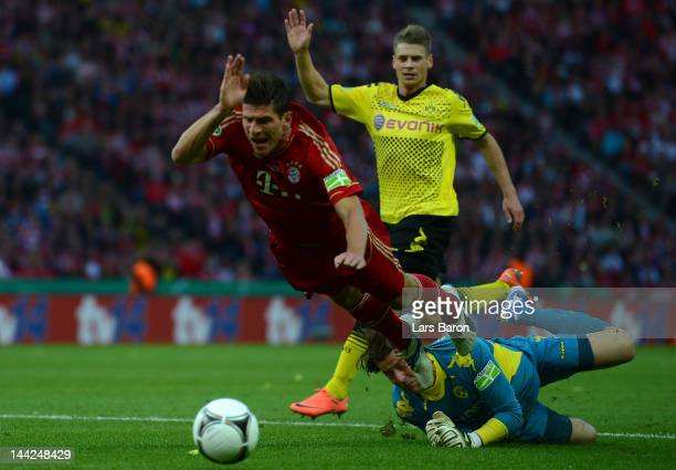 Mario Gomez of Muenchen is tackled in the penalty box by goalkeeper Roman Weidenfeller of Dortmund during the DFB Cup final match between Borussia...