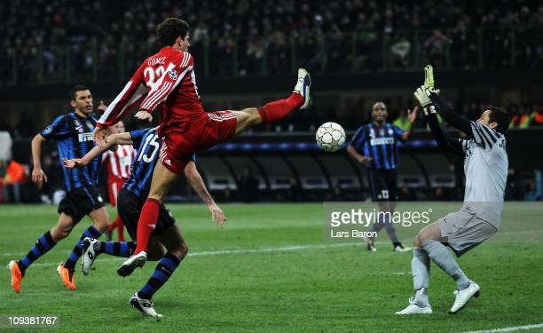 Mario Gomez of Muenchen jumpf for the ball next to goalkeeper Julio Cesar of Inter during the UEFA Champions League round of 16 first leg match...