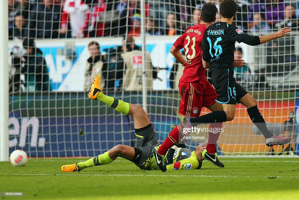 Mario Gomez (C) of Muenchen scores his team's first goal against goalkeeper Heurelho Gomes and Fabian Johnson of Hoffenheim during the Bundesliga match between TSG 1899 Hoffenheim and FC Bayern Muenchen at Rhein-Neckar-Arena on March 3, 2013 in Sinsheim, Germany.