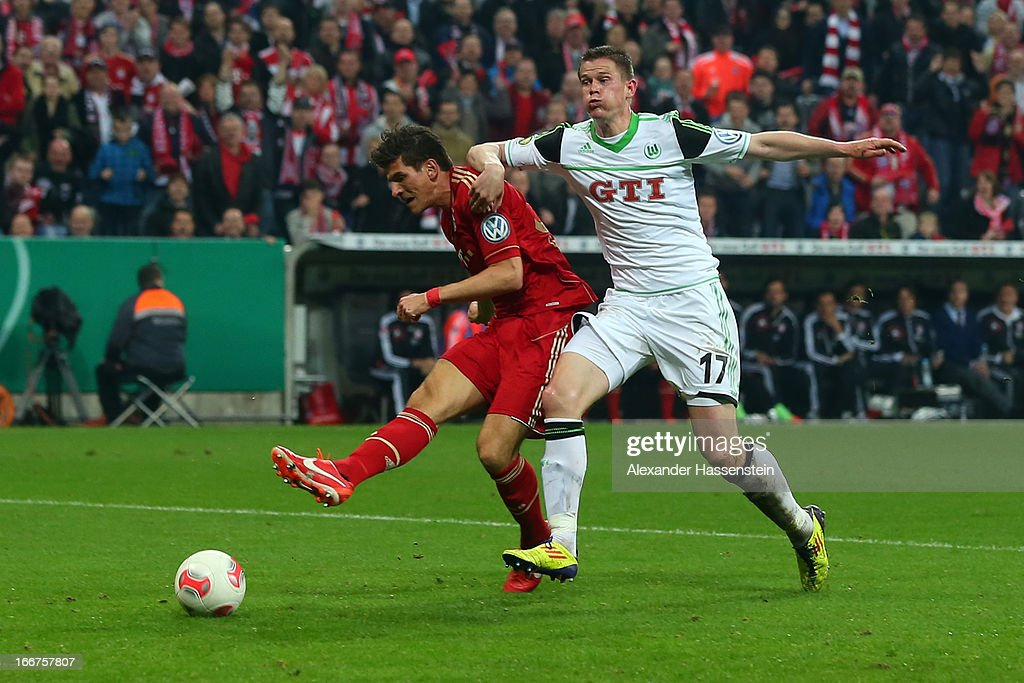 Mario Gomez (L) of Muenchen scores the 5th team goal against Alexander Madlung of Wolfsburg during the DFB Cup Semi Final match between Bayern Muenchen and VfL Wolfsburg at Allianz Arena on April 16, 2013 in Munich, Germany.