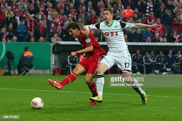 Mario Gomez of Muenchen scores the 5th team goal against Alexander Madlung of Wolfsburg during the DFB Cup Semi Final match between Bayern Muenchen...