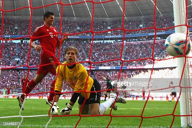 Mario Gomez of Muenchen scores the 5th team goal against Oliver Baumann keeper of Freiburg during the Bundesliga match between FC Bayern Muenchen and...