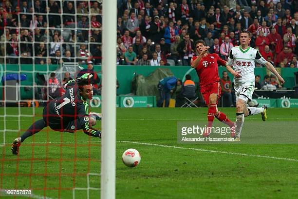 Mario Gomez of Muenchen scores the 6th team goal against Alexander Madlung of Wolfsburg and his keeoer Diego Benaglio during the DFB Cup Semi Final...