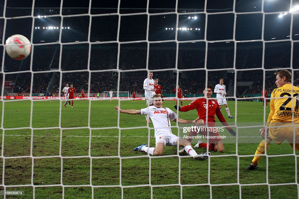 <a gi-track='captionPersonalityLinkClicked' href=/galleries/search?phrase=Mario+Gomez+-+Soccer+Player&family=editorial&specificpeople=635161 ng-click='$event.stopPropagation()'>Mario Gomez</a> (C) of Muenchen scores the opening goal against Ragnar Klavan (L) of Augbsurg and his keeper <a gi-track='captionPersonalityLinkClicked' href=/galleries/search?phrase=Alexander+Manninger&family=editorial&specificpeople=167082 ng-click='$event.stopPropagation()'>Alexander Manninger</a> during the DFB cup round of sixteen match between FC Augsburg and FC Bayern Muenchen at SGL Arena on December 18, 2012 in Augsburg, Germany.