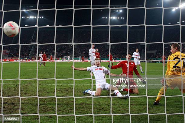 Mario Gomez of Muenchen scores the opening goal against Ragnar Klavan of Augbsurg and his keeper Alexander Manninger during the DFB cup round of...