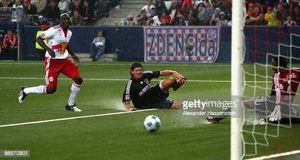 Mario Gomez of Muenchen shots towards the goal while Ibarhim Sekagaya of Salzburg looks on during the preseason friendly match between Red Bull...