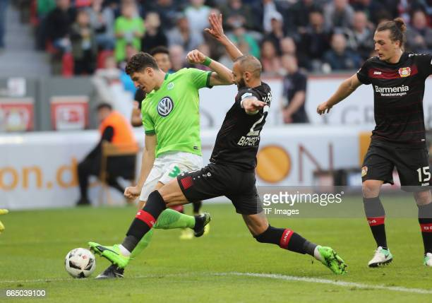 Mario Gomez of Wolfsburg and Oemer Toprak of Leverkusen and Julian Baumgartlinger battle for the ball during the Bundesliga match between Bayer 04...