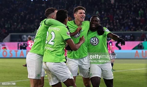 Mario Gomez of Wolfsburg celebrates after scoring his team's opening goal with Luiz Gustavo Borja Mayoral and PaulGeorge Ntep of Wolfsburg during the...