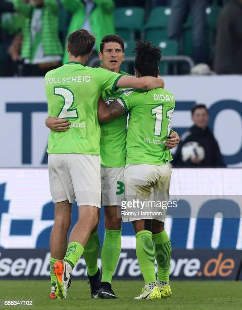 Mario Gomez of Wolfsburg celebrates after scoring his team's opening goal with Philipp Wollscheid and Daniel Didavi of Wolfsburg during the...