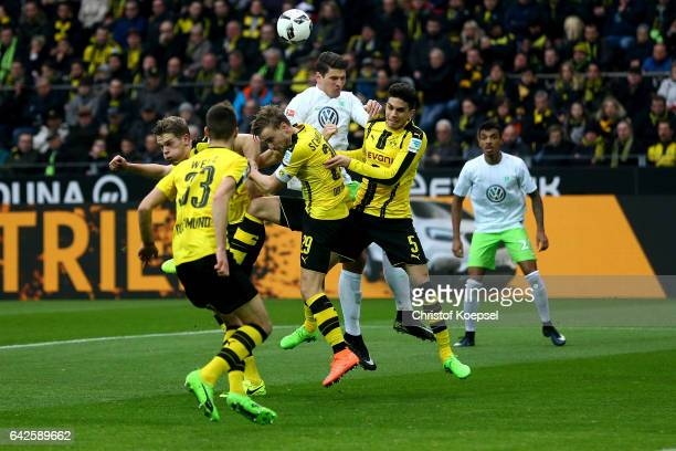 Mario Gomez of Wolfsburg goes up for a header against dwei Marcel Schmelzer and Marc Bartra of Dortmund during the Bundesliga match between Borussia...