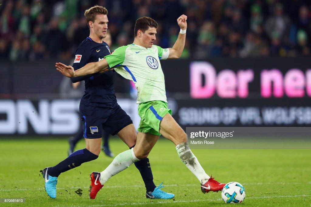 Mario Gomez of Wolfsburg scores his team's second goal under pressure from Sebastian Langkamp of Berlin during the Bundesliga match between VfL Wolfsburg and Hertha BSC at Volkswagen Arena on November 5, 2017 in Wolfsburg, Germany.