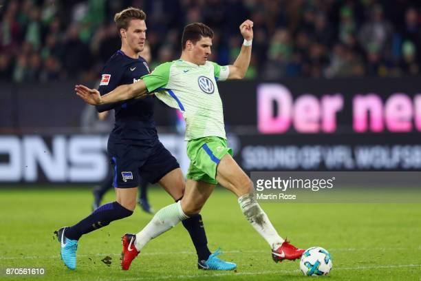 Mario Gomez of Wolfsburg scores his team's second goal under pressure from Sebastian Langkamp of Berlin during the Bundesliga match between VfL...
