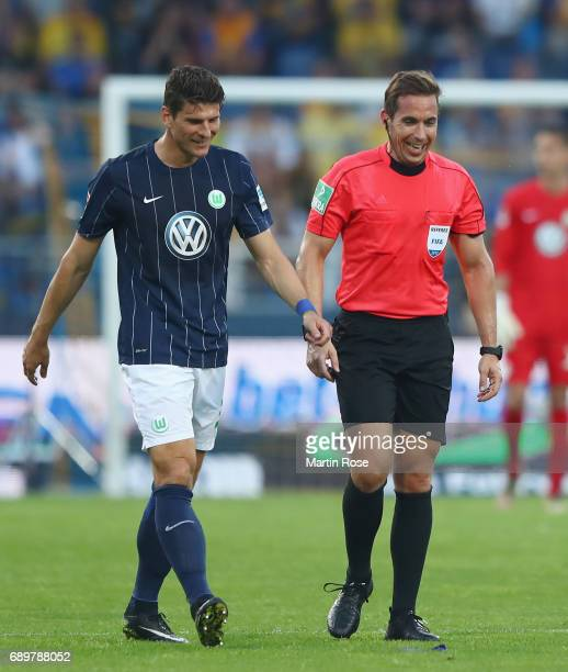 Mario Gomez of Wolfsburg walks next to referee Tobias Stieler during the Bundesliga Playoff leg 2 match between Eintracht Braunschweig and VfL...