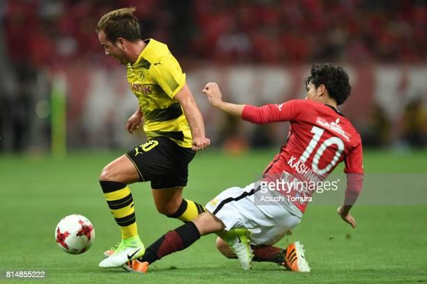 Mario Gotze of Borussia Dortmund is tackled by Yosuke Kashiwagi of Urawa Red Diamonds during the preseason friendly match between Urawa Red Diamonds...