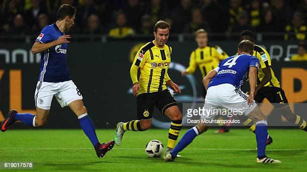 Mario Gotze of Borussia Dortmund runs at defenders Leon Goretzka and Benedikt Howedes of Schalke during the Bundesliga match between Borussia...