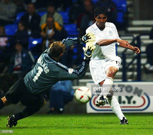 Mario Jardel of Bolton shoots as James Walker the goalkeeper of Walsall rushes out during the Carling Cup second round match between Bolton Wanderers...