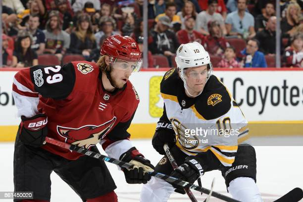 Mario Kempe of the Arizona Coyotes and Anders Bjork of the Boston Bruins get ready during a second period faceoff at Gila River Arena on October 14...