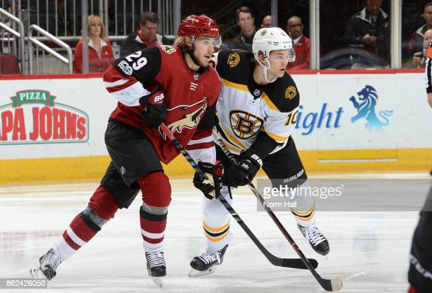 Mario Kempe of the Arizona Coyotes and Anders Bjork of the Boston Bruins get ready during a faceoff at Gila River Arena on October 14 2017 in...