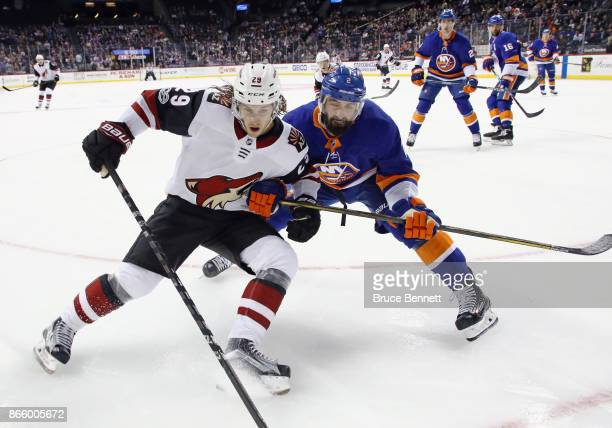 Mario Kempe of the Arizona Coyotes and Nick Leddy of the New York Islanders pursue the puck against the boards during the first period at the...