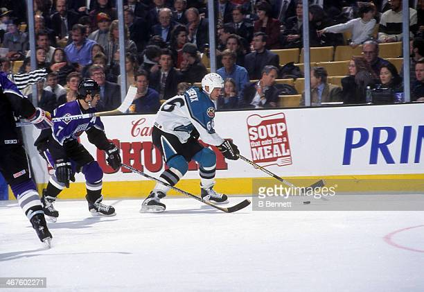 Mario Lemieux of the Eastern Conference and Pittsburgh Penguins skates with the puck as he is defended by Chris Chelios of the Western Conference and...