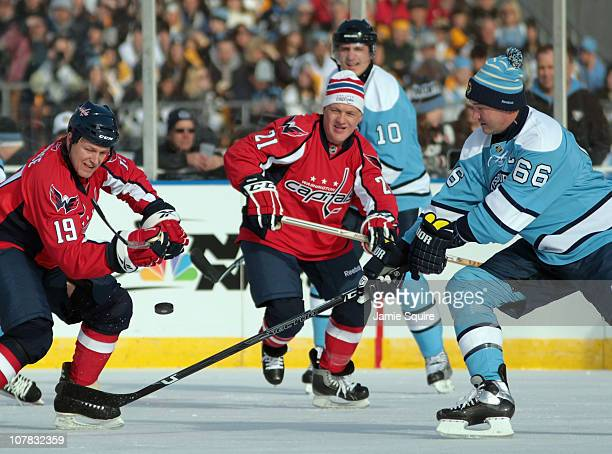 Mario Lemieux of the Pittsburgh Penguins battles John Druce and Dennis Maruk of the Washington Capitals for a loose puck during the 2011 NHL Winter...