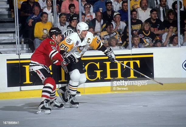 Mario Lemieux of the Pittsburgh Penguins battles with Steve Larmer of the Chicago Blackhawks during Game 1 of the 1992 Stanley Cup Finals on May 26...