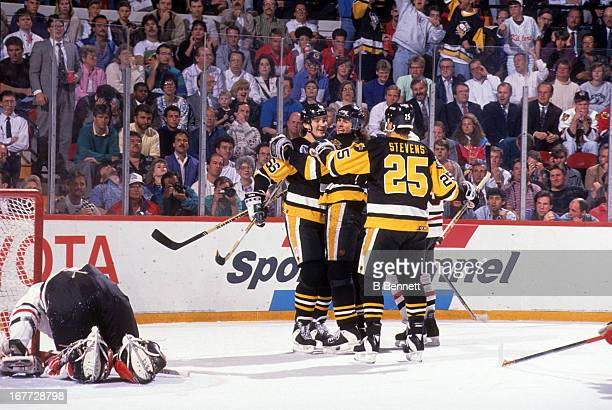 Mario Lemieux of the Pittsburgh Penguins celebrates with teammates Jaromir Jagr and Kevin Stevens as goalie Ed Belfour of the Chicago Blackhawks...