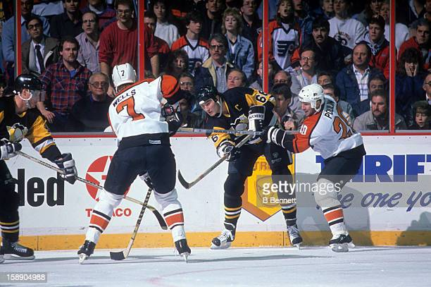 Mario Lemieux of the Pittsburgh Penguins is forced to pass the puck as he is pressured by Dave Poulin and Jay Wells of the Philadelphia Flyers on...