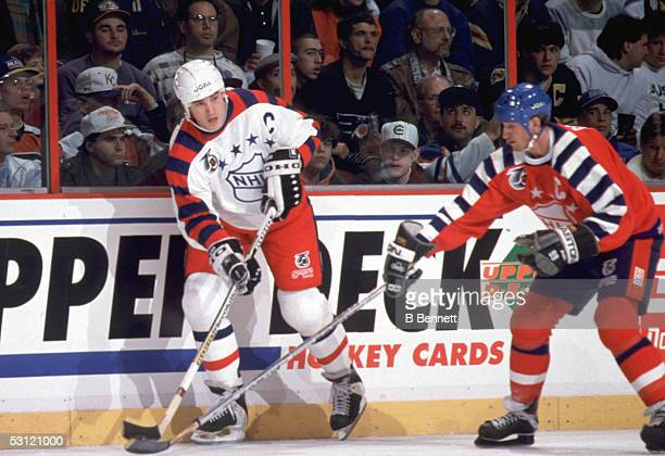 Mario Lemieux of the Wales Conference and the Pittsburgh Penguins skates with the puck as he is defended by Wayne Gretzky of the Campbell Conference...
