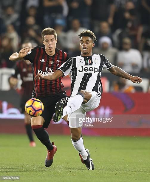 Mario Lemina of Juventus FC in action against Mario Pasalic of AC Milan during the Supercoppa TIM Doha 2016 match between Juventus FC and AC Milan at...
