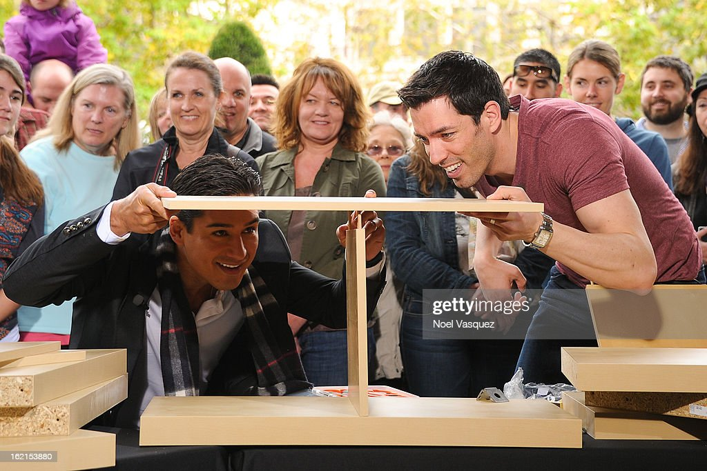 Mario Lopez (L) and <a gi-track='captionPersonalityLinkClicked' href=/galleries/search?phrase=Drew+Scott+-+Attore+canadese&family=editorial&specificpeople=15095917 ng-click='$event.stopPropagation()'>Drew Scott</a> build a bookshelf at Extra at The Grove on February 19, 2013 in Los Angeles, California.