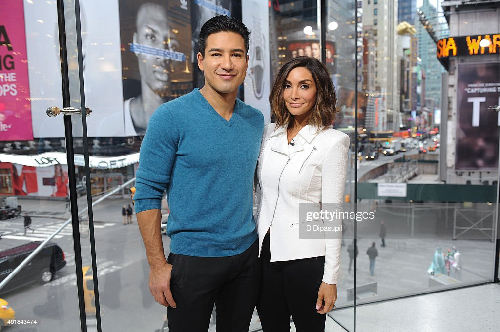 Mario Lopez and wife Courtney Mazza pose on the set of 'Extra' at their New York studios at HM in Times Square on January 20 2015 in New York City