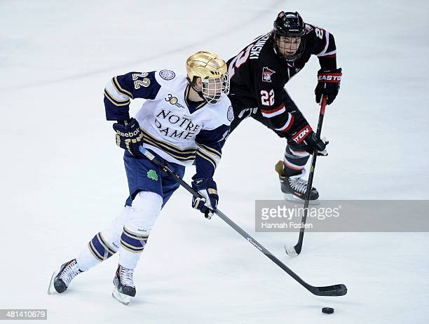 Mario Lucia of the Notre Dame Fighting Irish controls the puck against Jonny Brodzinski of the St Cloud State Huskies in overtime of the West...