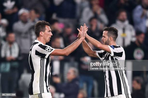 Mario Mandzukic and Miralem Pjanic celebrate at the end of the during the UEFA Champions League group D match between Juventus and Sporting CP at...