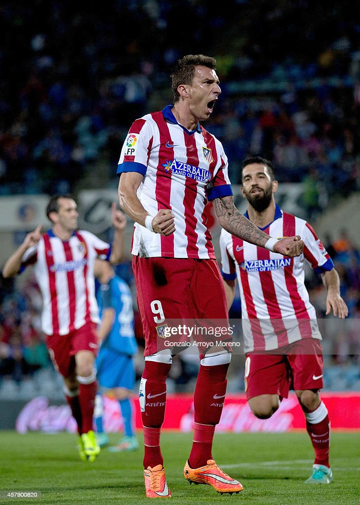 <a gi-track='captionPersonalityLinkClicked' href=/galleries/search?phrase=Mario+Mandzukic&family=editorial&specificpeople=4476149 ng-click='$event.stopPropagation()'>Mario Mandzukic</a> of Atletico de Madrid celebrates scoring their opening with teammates <a gi-track='captionPersonalityLinkClicked' href=/galleries/search?phrase=Arda+Turan&family=editorial&specificpeople=2179402 ng-click='$event.stopPropagation()'>Arda Turan</a> (R) and <a gi-track='captionPersonalityLinkClicked' href=/galleries/search?phrase=Diego+Godin&family=editorial&specificpeople=608999 ng-click='$event.stopPropagation()'>Diego Godin</a> (L) goal during the La Liga match between Getafe CF and Club Atletico de Madrid at Coliseum Alfonso Perez on October 26, 2014 in Getafe, Spain.