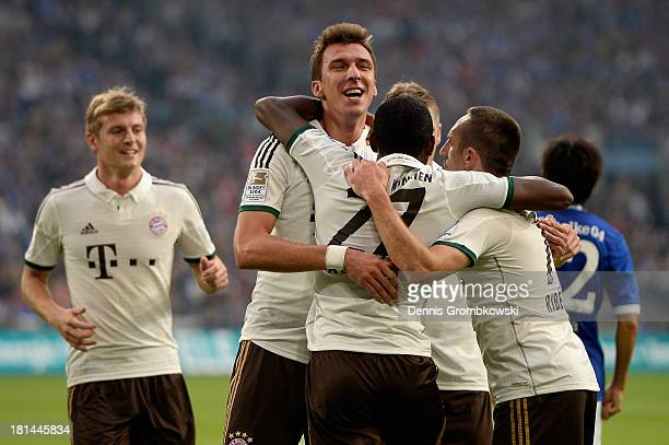 Mario Mandzukic of Bayern Muenchen celebrates with teammates after heading his team's second goal during the Bundesliga match between FC Schalke 04...